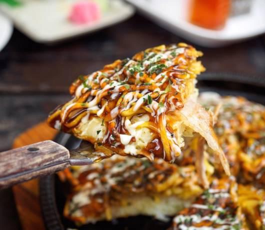 Okonomiyaki, czyli placki z kapustą i różnym składnikami polane słodkim sosem