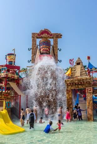 Od góry: Hotel Atlantis The Palm na sztucznej wyspie w kształcie palmy i liczne atrakcje w parku Aquaventure: sztuczna rzeka, tunel w basenie z rybami i wodny plac zabaw dla maluchów.